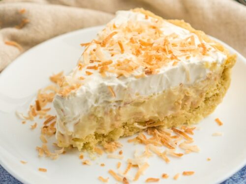 A slice of coconut cream pie on a plate topped with toasted coconut