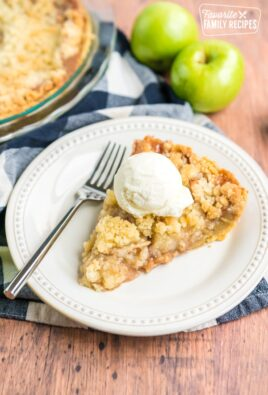 dutch apple pie on a plate with a fork and a scoop of ice cream on top