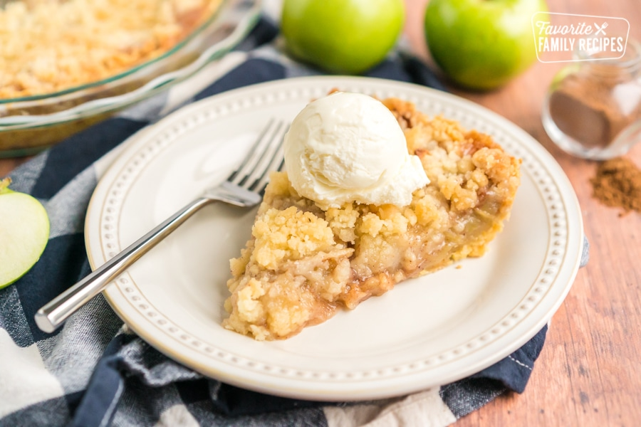 A slice of dutch apple pie on a plate with a scoop of ice cream on top