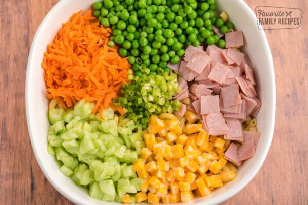 Ham, cheese, carrots, cucumbers, peas, and green onions all diced up in a white bowl