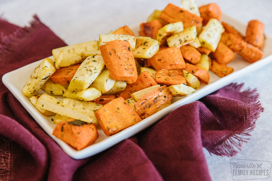 A white tray filled with roasted parsnips and carrots