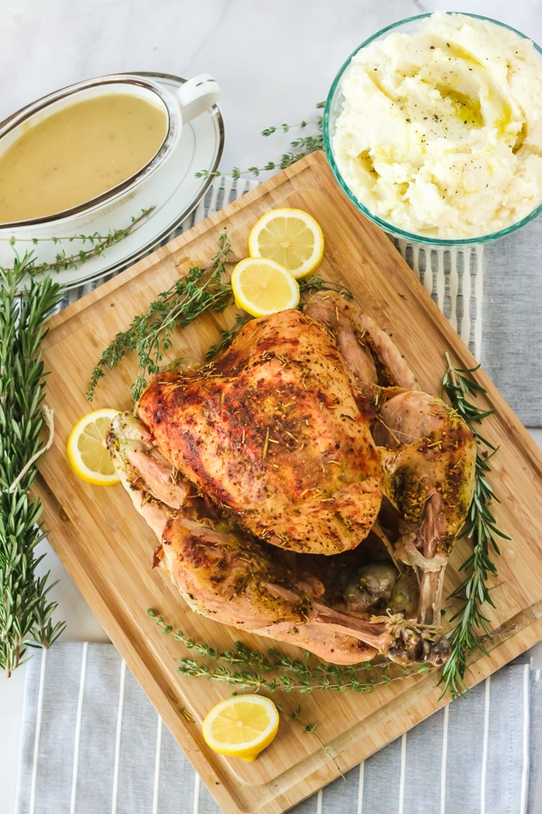 Turkey on a cutting board with mashed potatoes and gravy