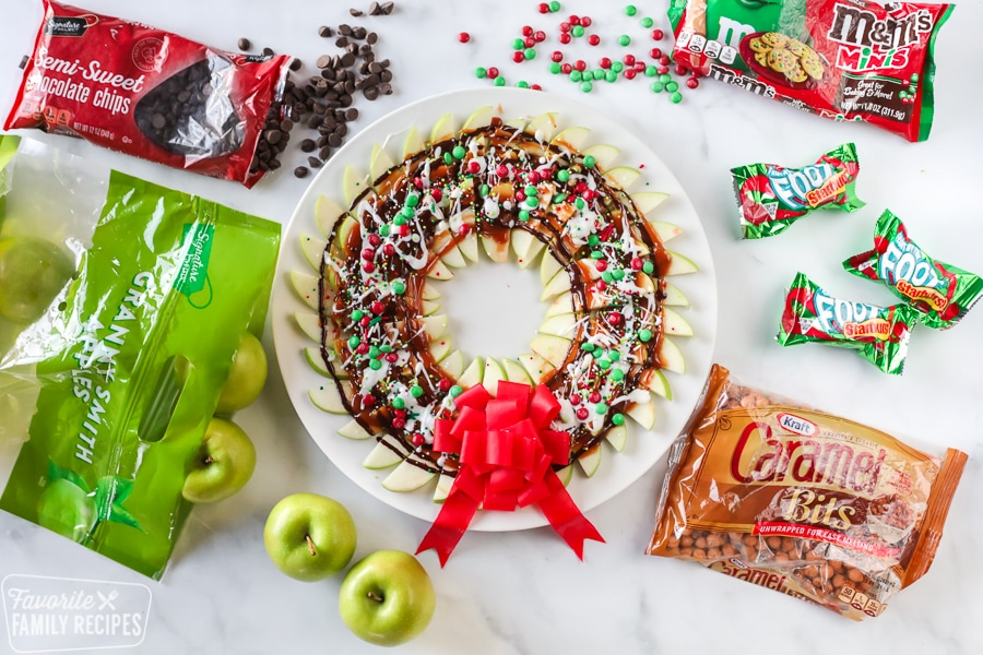 Apple wreath made from sliced apples, caramel, chocolate, and Christmas candies