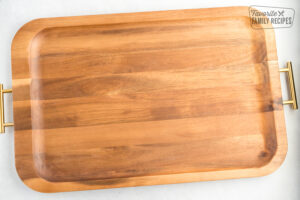 A wooden tray with gold handles