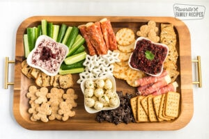 All the larger crackers, meats, and cheeses placed on a charcuterie board