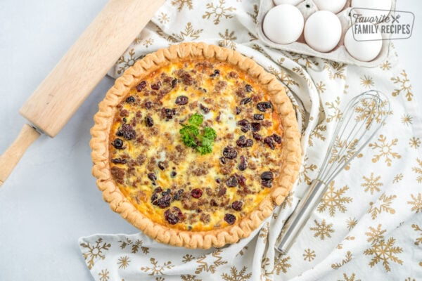 A Christmas Breakfast Quiche on the counter with a rolling pin, whisk, and egg carton