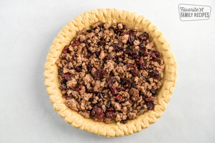 A pie crust filled with cheese, sausage, and cranberries