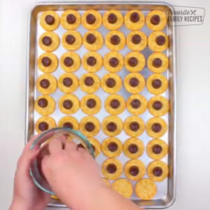 Adding Rolo candies to tops of ritz crackers