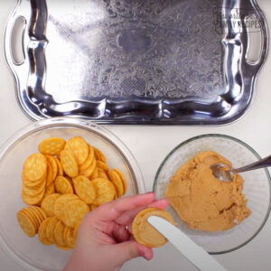 Spreading peanut butter on ritz crackers
