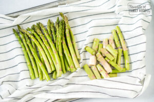 Trimmed asparagus on a dish cloth to make roasted asparagus in the oven