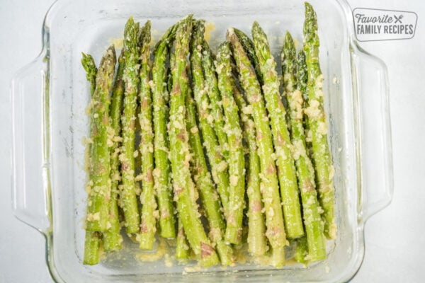 Asparagus tossed in olive oil, garlic, and cheese that has been roasted in a glass baking dish