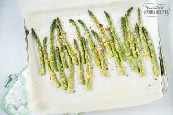 Roasted Asparagus on a baking sheet with parmesan cheese and seasoning