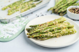 Roasted asparagus on a plate with cheese and seasonings.