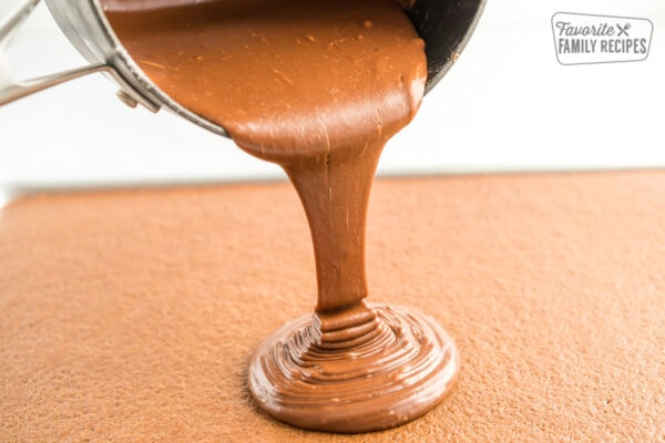 Chocolate frosting being poured onto a cake