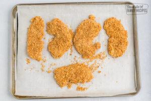 Breaded unbaked chicken tenders on a baking sheet