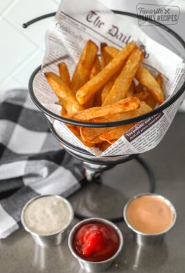 Air Fryer French Fries in a basket with 3 dipping sauces