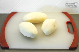 3 potatoes on a cutting board