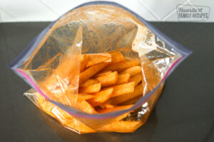 Tossing fries in oil and seasoning in a bag