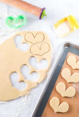 Sugar cookie dough rolled out and cut out with some on a baking sheet