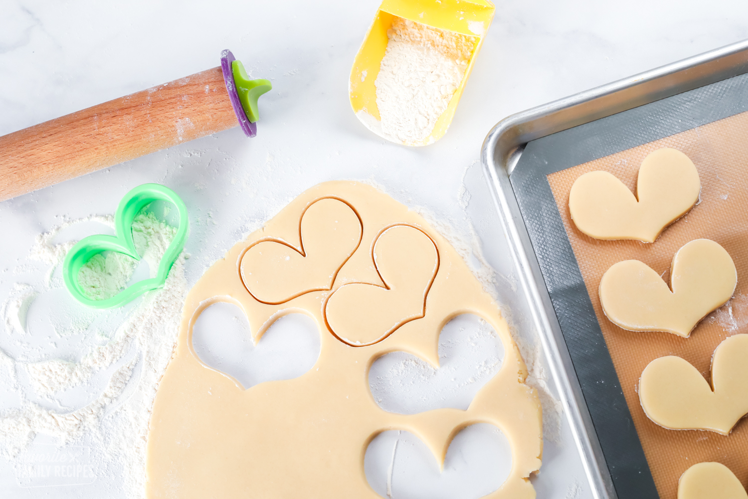 Sugar cookie dough with cut out cookies and places on a baking sheet
