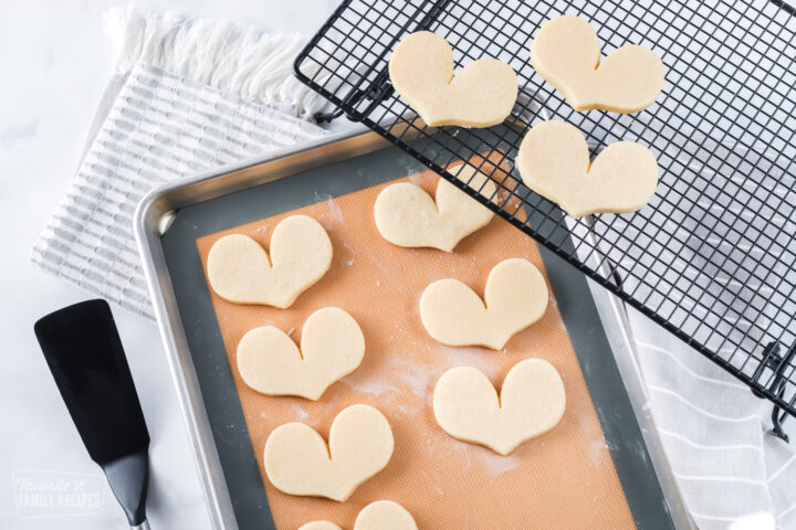 Baked sugar cookies on a baking sheet and cooling rack