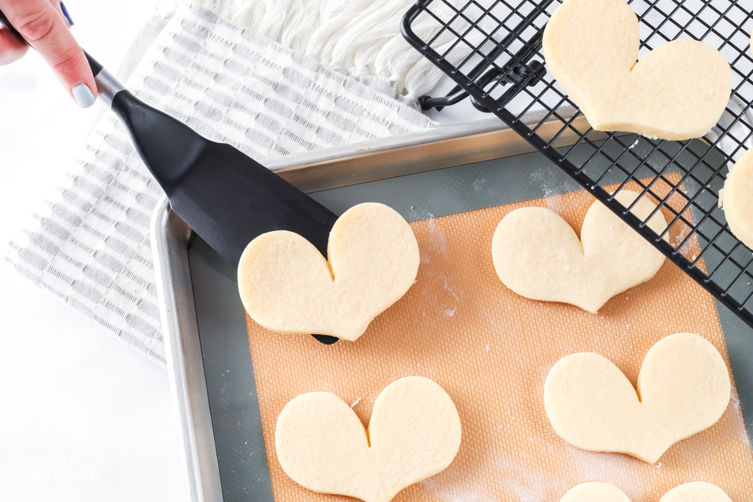 Sugar cookie being lifted from baking sheet with a spatula