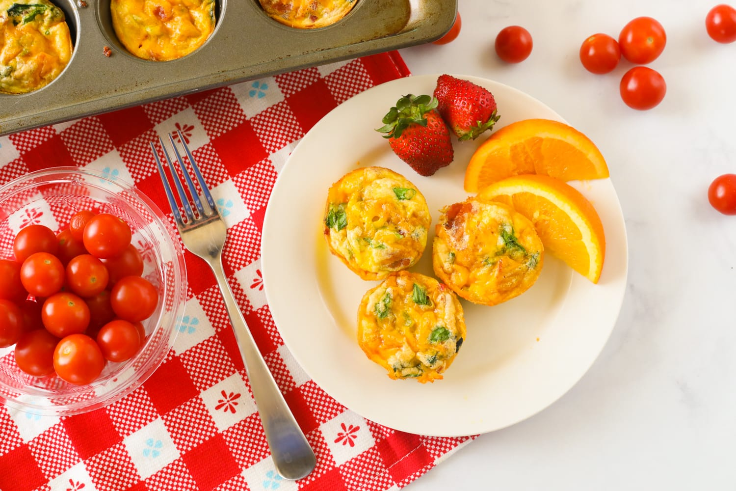 Breakfast egg muffins on a plate with fruit and tomatoes