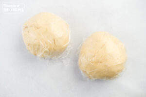 Two balls of homemade pizza dough wrapped in plastic wrap