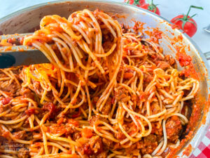 Spaghetti being served with tongs