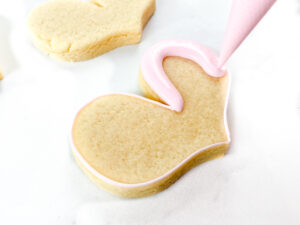 Sugar cookie with icing being piped on