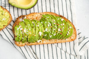 Toast with sliced avocado, feta, honey, and red pepper flakes