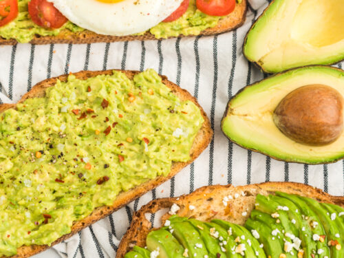 Three pieces of toast, one with mashed avocado, salt, and pepper, one with sliced avocado, feta, and honey, and one with mashed avocado, tomato, and a fried egg