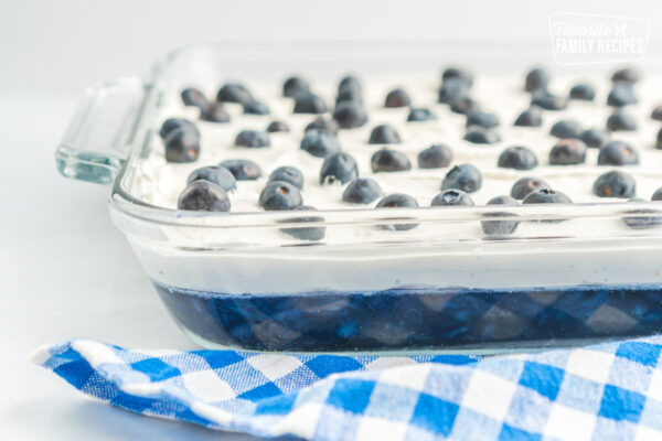 Blueberry Jello Salad topped with fresh blueberries in a glass baking dish