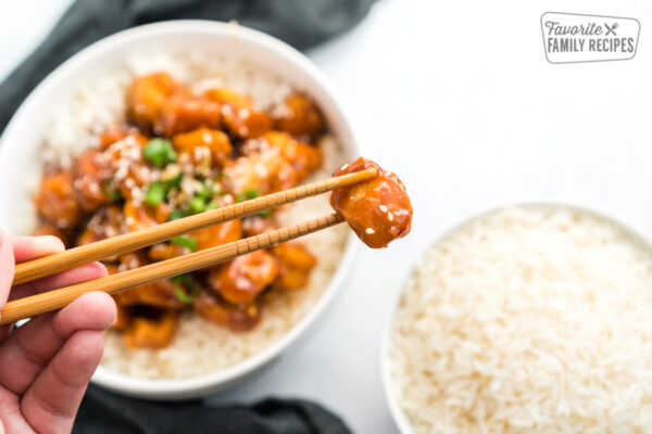 A piece of General Tso's Chicken held up with chopsticks