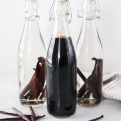 Two bottles of newly made vanilla extract with vanilla beans and one bottle of mature vanilla extract