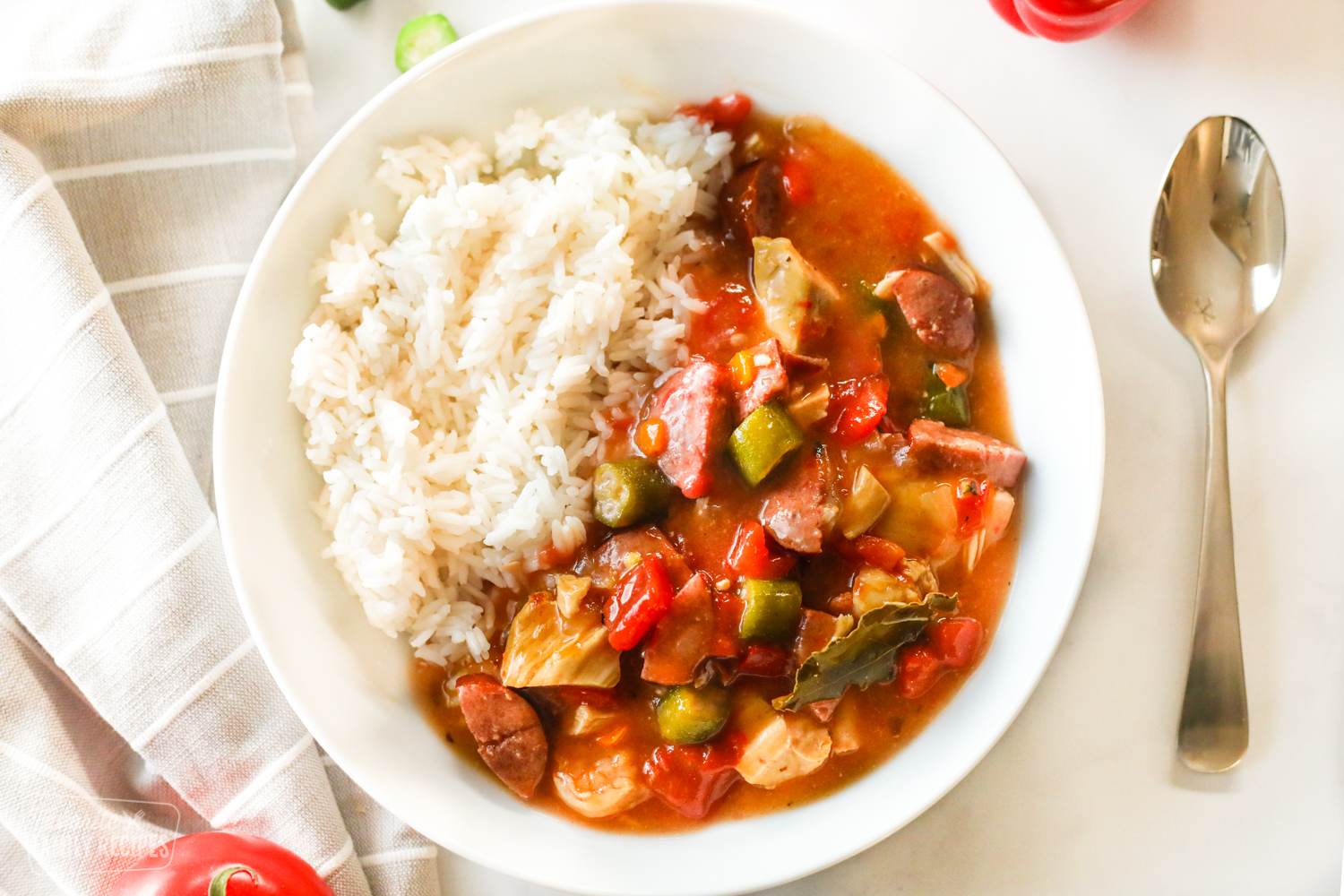 A bowl of Instant Pot Gumbo with chicken, sausage, shrimp, peppers, onion, and okra with rice on the side