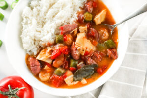 A bowl of Instant Pot gumbo made with chicken, sausage, shrimp, peppers, onions, okra, and seasonings with rice served on the side.