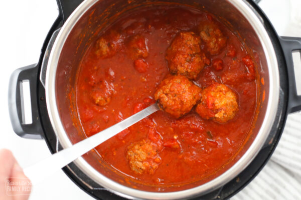 Meatballs in an Instant Pot being served with a serving spoon