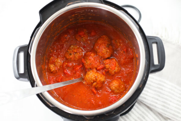 Meatballs in red sauce in an Instant Pot with a serving spoom