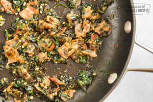 Spinach, bacon, garlic, and oil cooking in a skillet