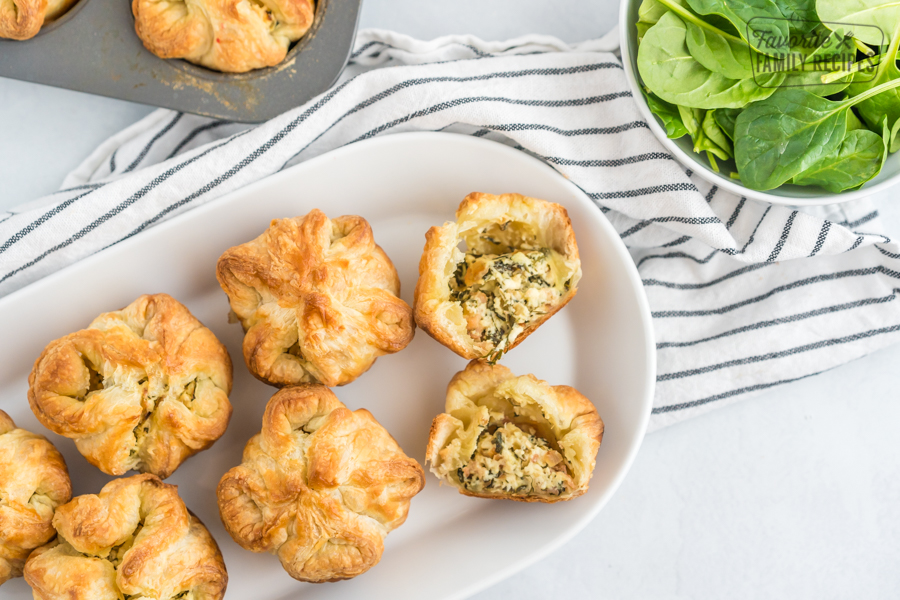 Spinach Puffs on a white plate with one cut open to reveal the cheese and spinach filling