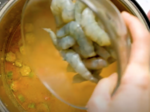 Shrimp being added to gumbo that has been made in an Instant pot