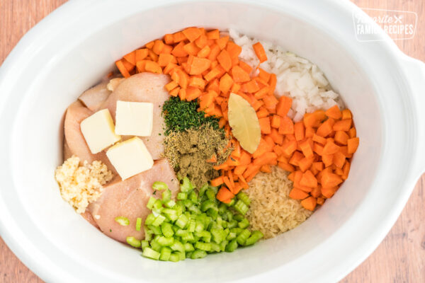 Chicken, carrots, onions, rice, butter, garlic, celery, and spices in a slow cooker