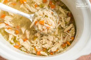 A ladle full of slow cooker chicken and rice soup