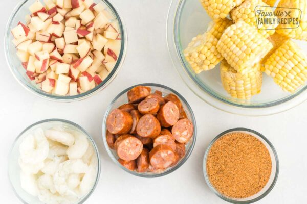 Little glass bowls, each one filled with a different ingredient: corn potatoes, sausage, shrimp, and Cajun Seasoning