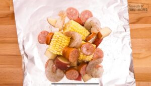 A piece of tin foil topped with shrimp, potatoes, corn, and sausage