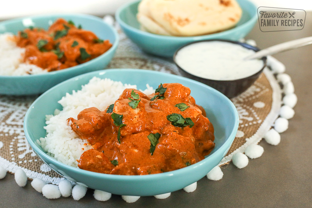 A blue bowl filled with Chicken Tikka Masala and rice. Naan bread and yogurt on the side.