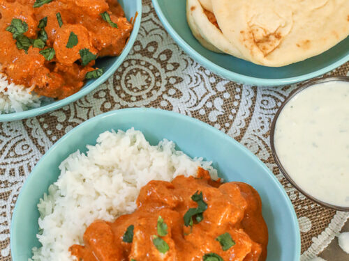 Chicken Tikka Masala in a bowl with rice and a side of yogurt dip and naan bread