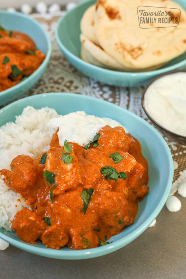 Chicken Tikka Masala in a bowl with rice and cucumber yogurt dip