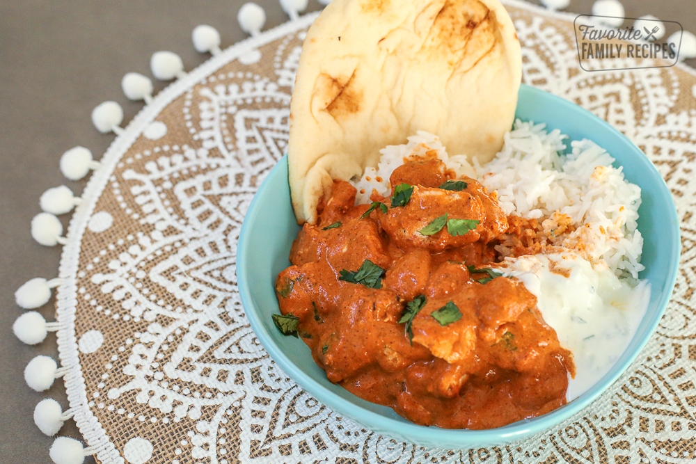 Chicken Tikka Masala in a blue bowl with rice, yogurt, and naan bread.